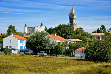 Bell tower church and castle among trees of Noirmoutier en l'Ile in Pays de la Loire, region in western France
