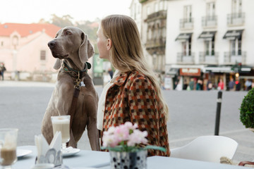 Woman sitting in a cafe with her Weimaraner dog. Fotobehang
