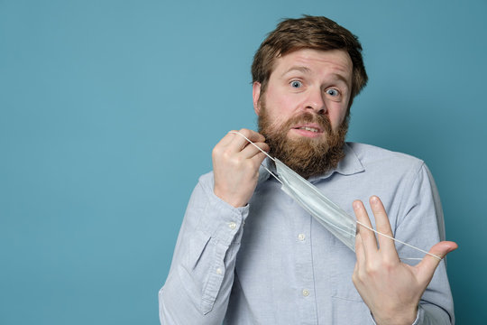 Man is bewildered, confused, he is holding a medical mask in hands and does not know how to put it on a shaggy beard. Copy space.