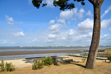 Beach at low tide of Saint Brevin les Pins in Pays de la Loire region in western France, and the town of Saint Nazaire in the background