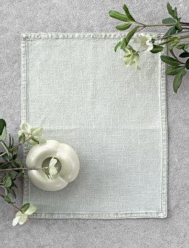 Light green ceramic vase, spring flowers and linen napkin on concrete background.