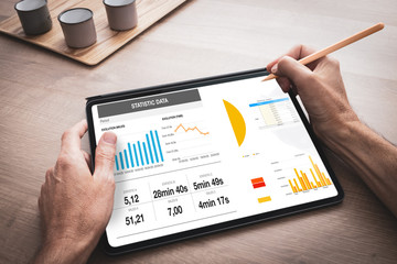 Tablette numérique tenue en main par un homme au travail avec une présentation d'affaires avec des graphiques de données et des statistiques
