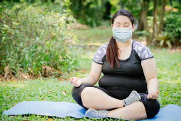 Foto op Plexiglas Lotusbloem Asian fat girl doing yoga meditation at outdoor public green park and wear face mask for virus spreading protection.