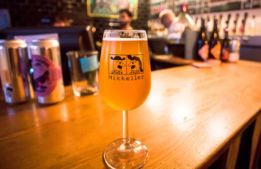 Craft beer bar with glass of popular danish beer by Mikkeller brewery, in special designed glass