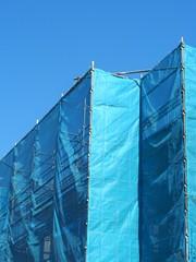 青いシートで覆われた建設中の建物
