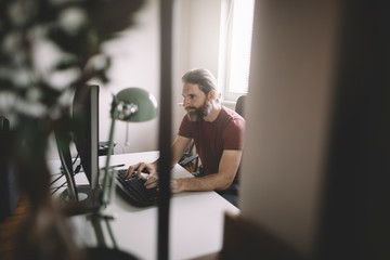 Ginger bearded man working on computer from his home office