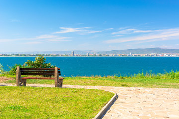 bench on the sunny beach shore. beautiful skyline view from empty park with paved footpath on the seaside. city and mountain in the distance beneath a blue sky with clouds
