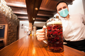 Masked bartender serving a giant beer