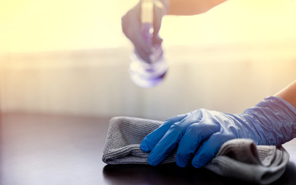 Hands wear blue rubber gloves to prevent germs and use disinfectant sanitizing spray cleaning table business office to disinfecting coronavirus and prevention against Coronavirus disease 2019, COVID
