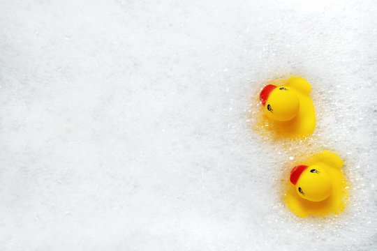High Angle View of yellow rubber duck in bath swimming in foam water. Yellow rubber ducklings in soapy foam.