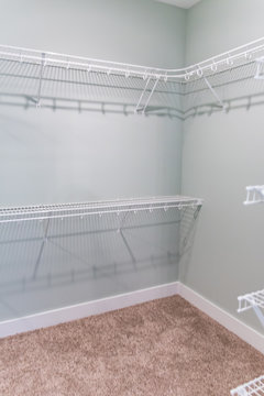 Empty master bedroom walk-in closet with wire shelving