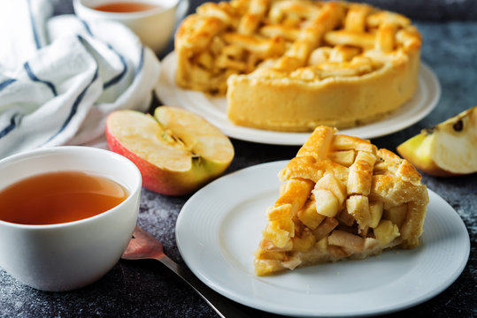 Apple cake with fresh apple slices and cups of tea