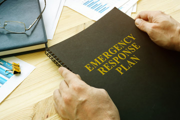 Man open disaster and emergency response plan for reading.