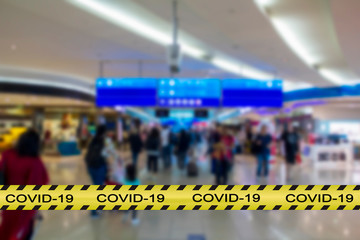 Covid-19 warning tape with blurred airport image on the background. Coronavirus spread and...