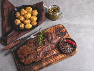Fototapete - grilled beef steak with bone on a cutting board, roasted new potatoes in a pan, spices