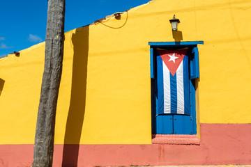 Deurstickers Havana Cuban flag in a blue window with a yellow wall