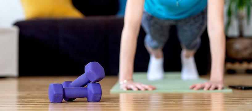 woman doing exercise at home stay fit indoors focus on dumbells
