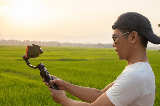 Man holding a gimbal with a phone in evenning