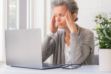 Close up of middle age woman with laptop rubbing temples and closing eyes (selective focus)