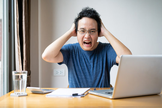 Young Asian businessman in relax casual during working from home. Asian man staying at home and setup a small workplace during COVID-19 self isolation. Work from home concept during coronavirus crisis