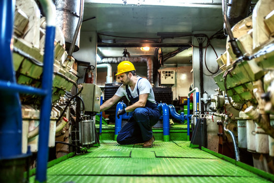Worthy caucasian mechanic in overalls and with helmet kneeling inside ship and repairing engine.