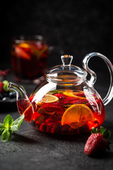 Fruit red tea with berries in glass teapot on black background