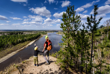 Vedenshina, Russia - April 29, 2020: Young mother shows her child a beautiful landscape in spring Irkut river with sky clouds. View from above, Siberia