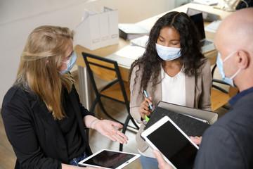 Mitarbeiter in einem Büro tragen Masken und haben eine Besprechung