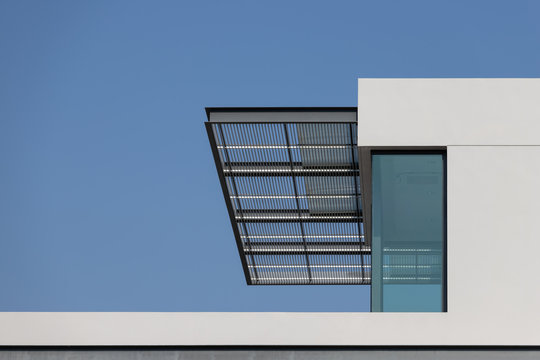 steel awning of modern house. exterior metal louver shading against blue sky.