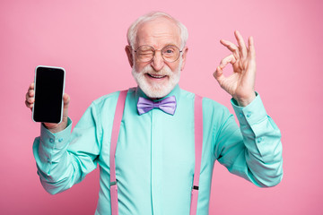 Portrait of energetic positive old man hold new cellphone show okay sign recommend choose good modern technology wear teal turquoise shirt violet bow tie isolated pastel pink color background