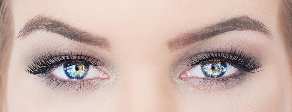 woman with beautiful blue eyes with long eyelashes. hypnotic look closeup. smoky eyes make up
