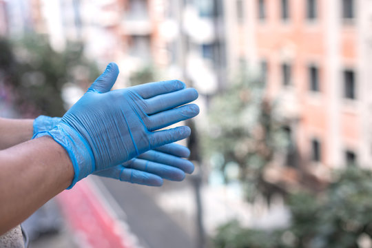 Male hands with blue gloves clapping outside the window during the quarantine for Covid 19 as a sign of appreciation for health personnel and law enforcement.