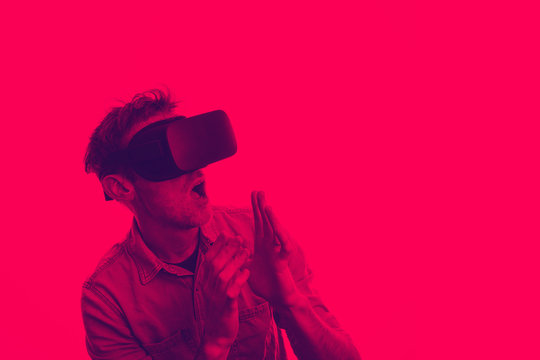 Man in his 30's wearing a VR virtual reality headset. Graphic duotone style