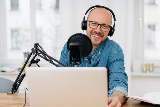 Happy friendly man recording a podcast