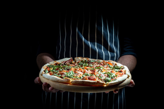 Man holding plate with tasty Italian pizza, close up view on a dark background