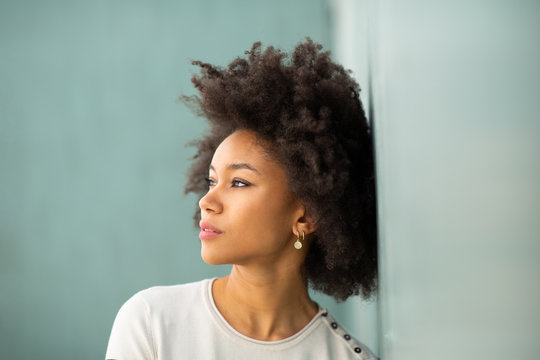 Close up young african american woman with afro hair leaning against wall looking away