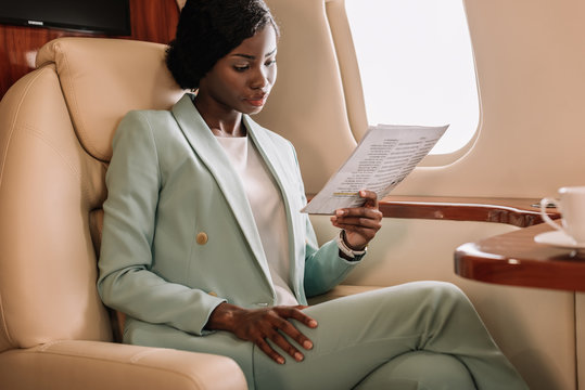concentrated african american businesswoman reading document in private jet