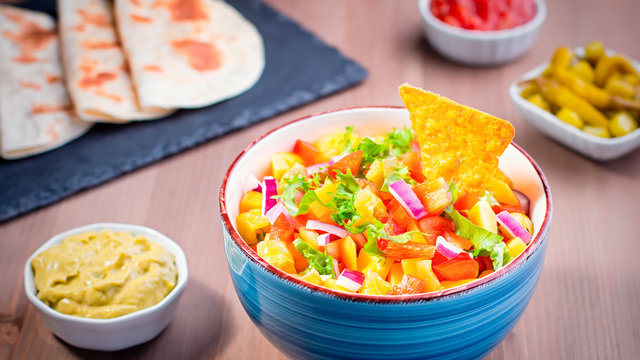 Mango salsa close up with jalapeno peppers, tortillas and lime. Traditional dish and appetizer for Cinco de Mayo celebration party.