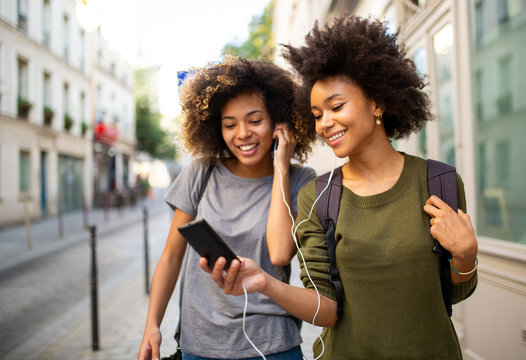 two female black friends walking in city with mobile phone listening to music with earphones