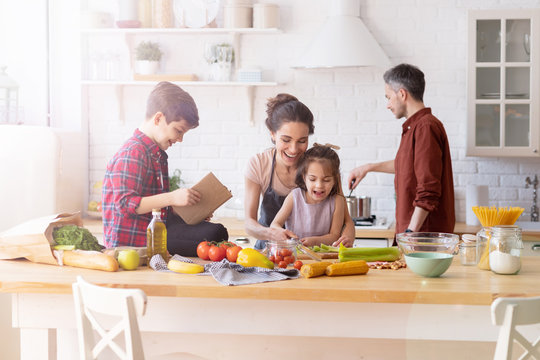 Children and parents cook together at home in the kitchen