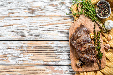 Garden Poster Steakhouse Grilled outside skirt steak on a chopping Board. White background. Top view. Copy space