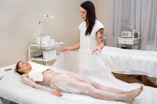 Cosmetic procedure wraps. The beautician covers the young girl with cellophane for anti-cellulite hydro-massage in a modern cosmetology room. Moisturizing body mask and body wrap.