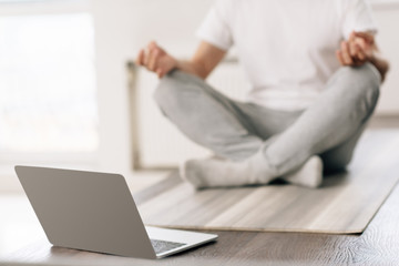 selective focus of laptop near man sitting in lotus pose at home
