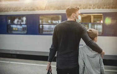 young family waiting for Train, young father with son in front of train in train station wearing a face mask