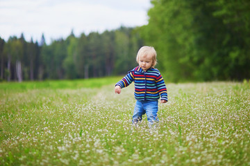 Adorable baby girl walking on field