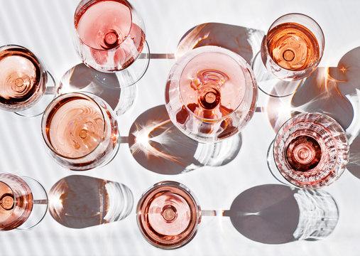 verschieden Gläser gefüllt mit Roséwein isoliert auf weiß