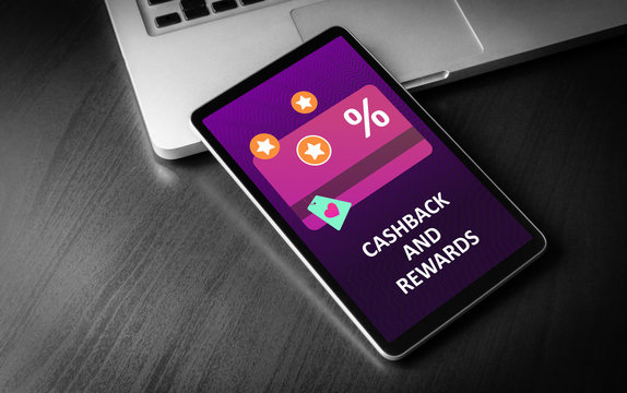 Cashback and Rewards - loyalty program and retail customer money refund service concept. Tablet PC lying on a wooden table with discount card with rewarding marketing points on the screen.
