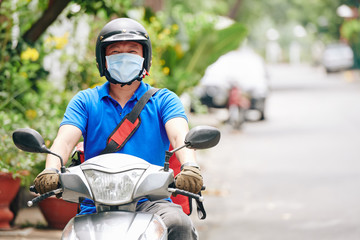 Courier in helmet and medical mask riding on scooter when delivering food to customers staying home...