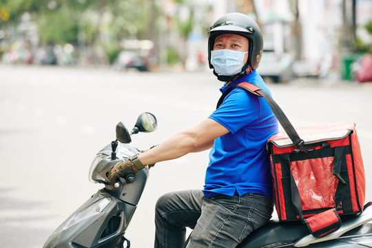 Cheerful Vietnamese delivery man sitting on scooter with cooler bag and delivering food during pandemic