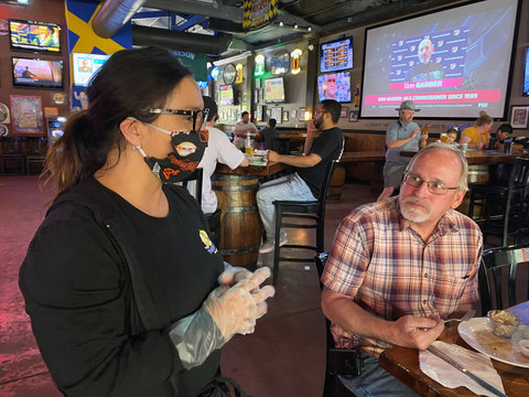 Restaurant owner Sandee Drown talks with customer Tim Schmidt at the Happy Viking Sports Pub and Eatery after opening following coronavirus disease (COVID-19) restrictions in Yuba City